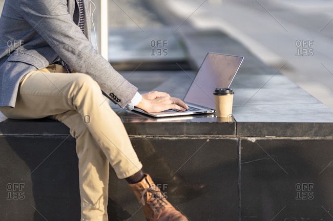 Businessman with coffee cup using laptop while sitting on bench