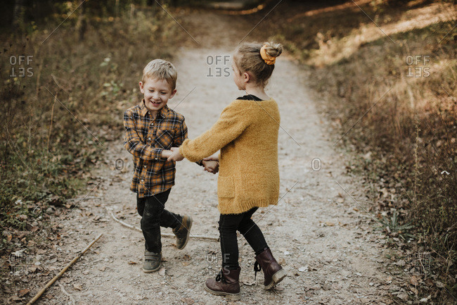 Smiling girl and brother holding hands while playing in forest