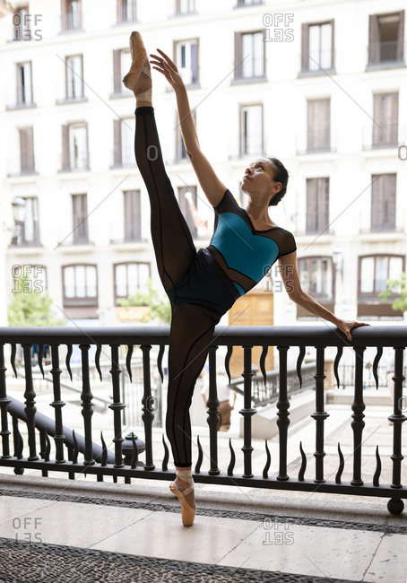 Female ballet dancer dancing while standing by railing in city