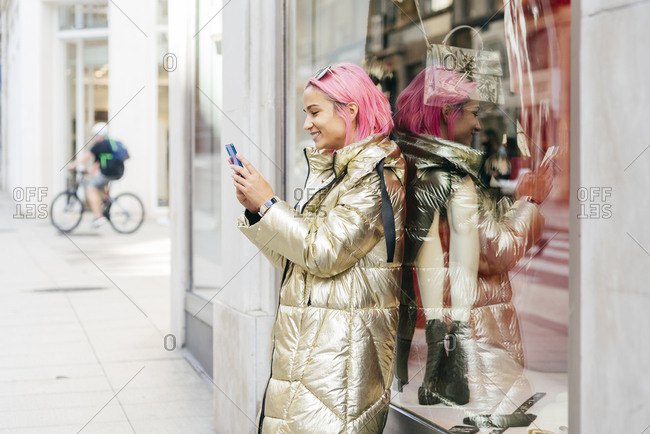 Smiling woman using mobile phone while leaning on store window