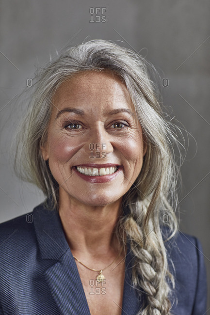 Happy businesswoman with gray hair against wall at home office