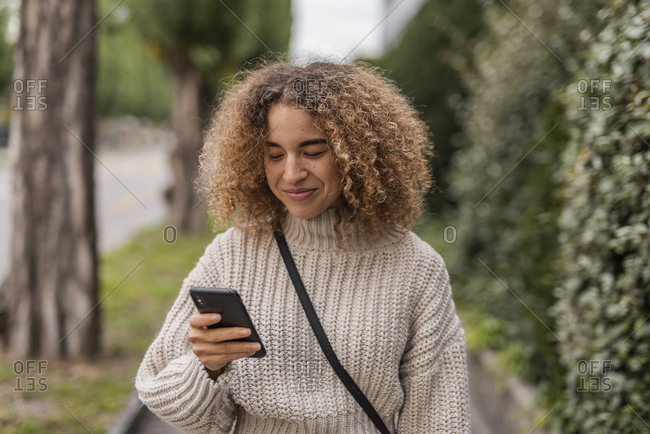 Smiling young woman text messaging through smart phone in city