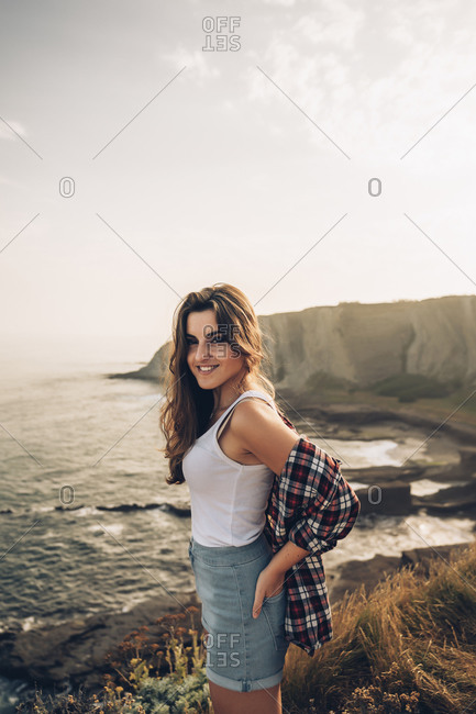 Beautiful young woman with hand in pocket standing against sky