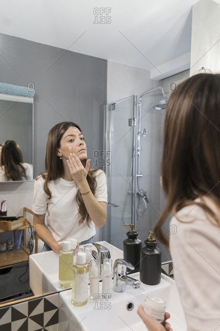 Woman applying facial cream while standing in bathroom at home