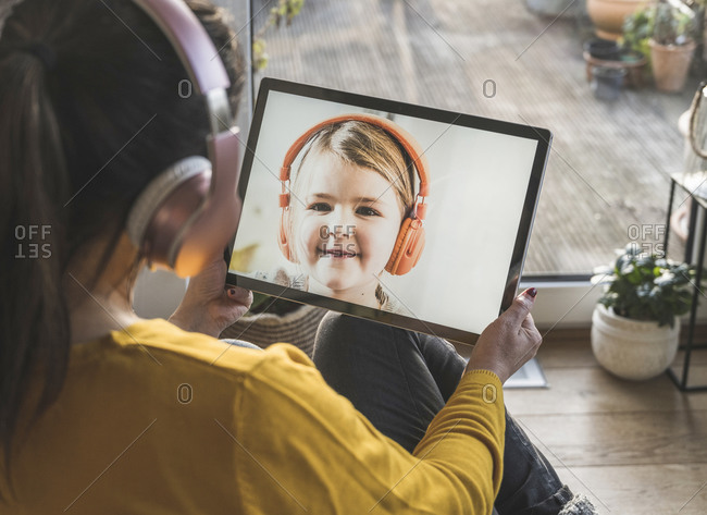 Little girl smiling on digital tablet screen during video call