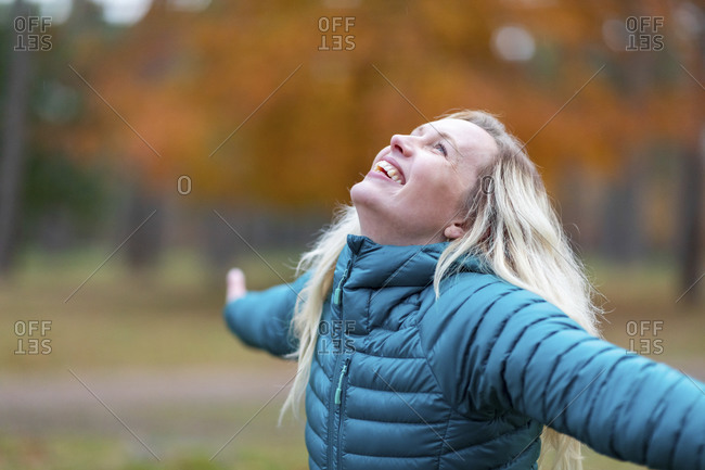 Happy woman with arms outstretched looking up at Cannock Chase