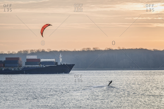 Kiteboarder surfing in front of passing container ship at dawn