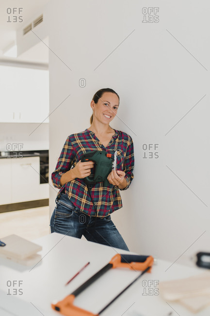 Mid adult woman smiling while holding electric jigsaw at home