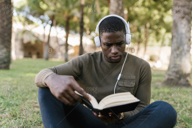 Male entrepreneur reading book while sitting on grass in park