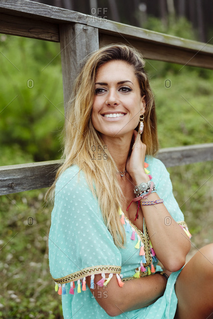 Smiling woman looking away while sitting by railing at forest