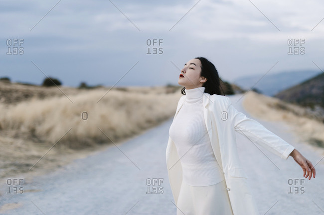 Woman with eyes closed and arms outstretched standing on road