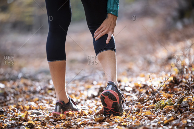 Sportswoman having cramp in leg while standing on forest path