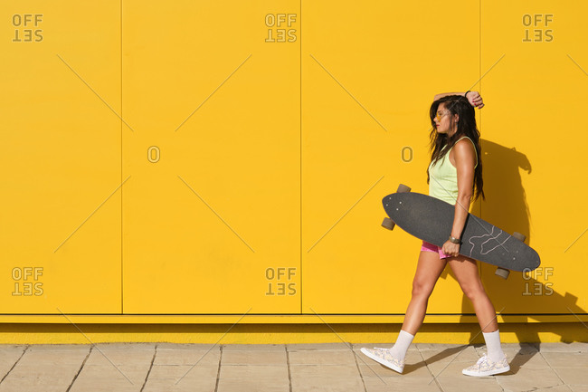 Young woman walking along yellow wall with longboard in hand