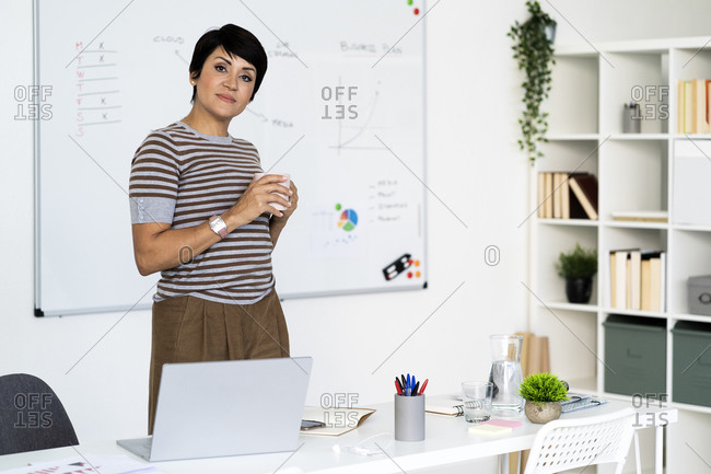 Portrait of businesswoman posing in office with mug in hands