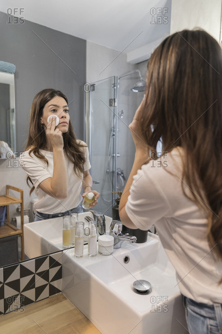 Young woman doing make-up while standing in bathroom at home