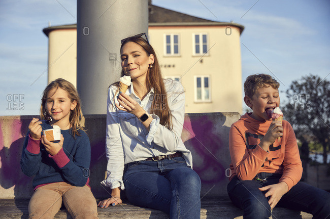 Mother having ice cream with children while sitting on bench
