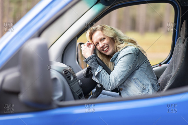 Woman laughing while leaning on steering wheel in motor home