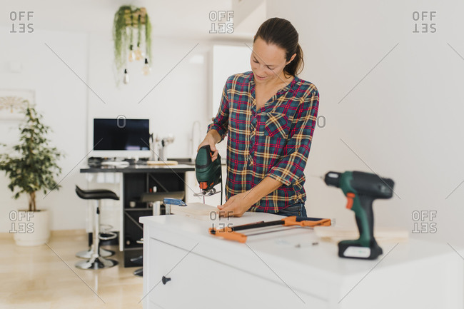 Woman cutting wood with electric saw while standing at home