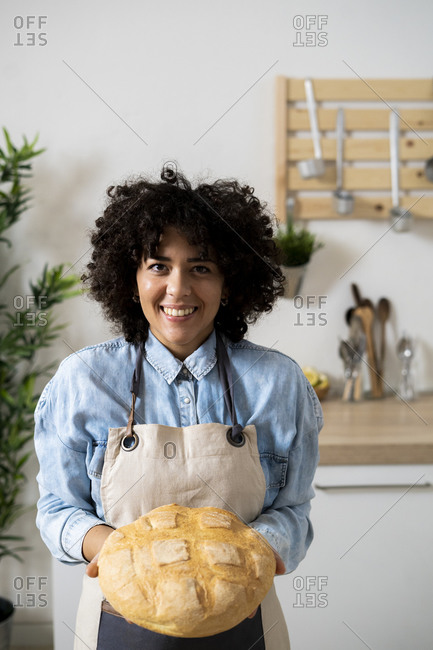 Portrait of young woman holding freshly baked loaf of bread
