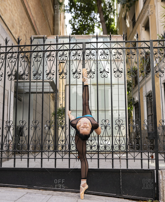 Ballet dancer stretching legs on gate while dancing in city