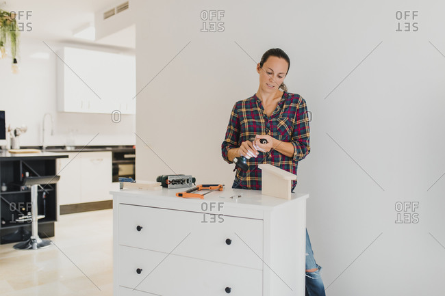 Woman changing drill bit while standing by cabinet at home