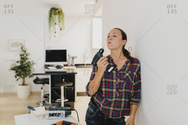 Woman holding electric drill while leaning on wall at home