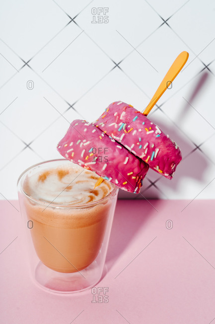 Coffee cup with pink doughnuts in spoon on kitchen table