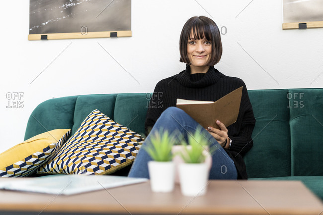 Smiling woman with book sitting on sofa in living room