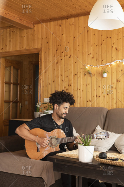 Young man playing guitar while sitting on sofa at home