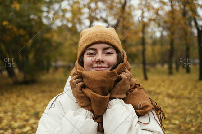 Smiling young woman wrapped up in scarf in autumn park