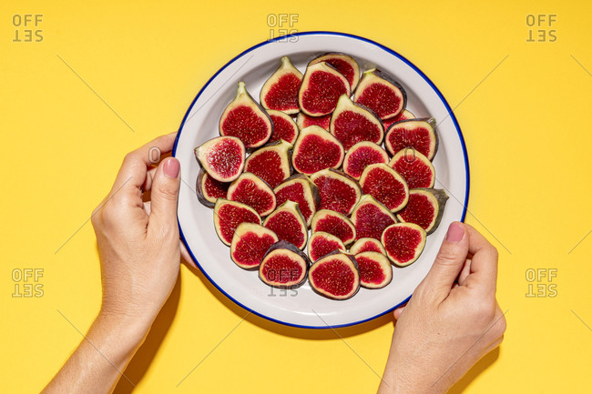 Hands of woman picking up plate with fresh halved figs