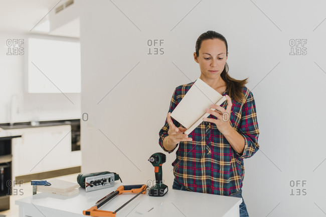 Mid adult woman doing DIY work while standing at home