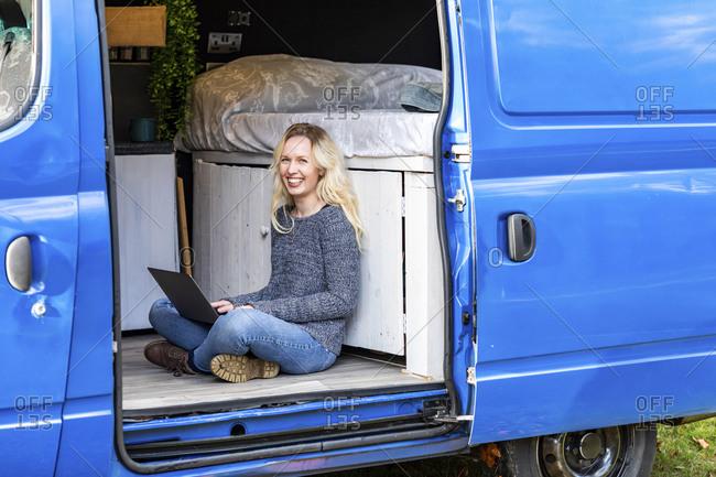 Happy woman with laptop sitting at door of camper van