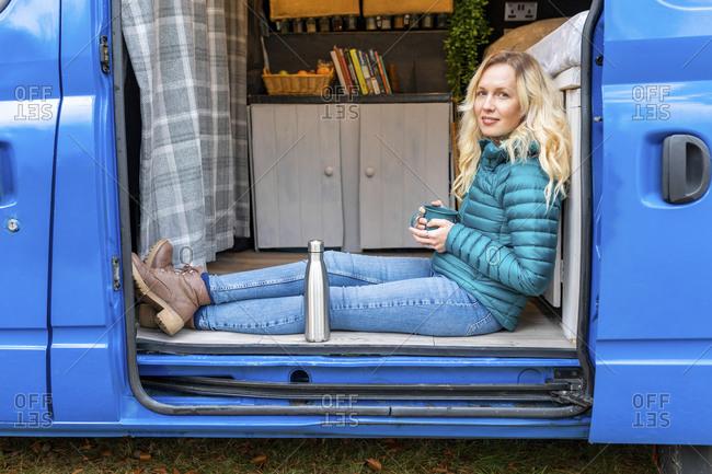 Smiling woman with tea cup relaxing at door of van