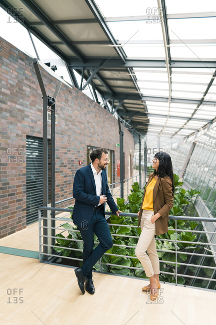 Female entrepreneur discussing with male colleague while standing corridor of office