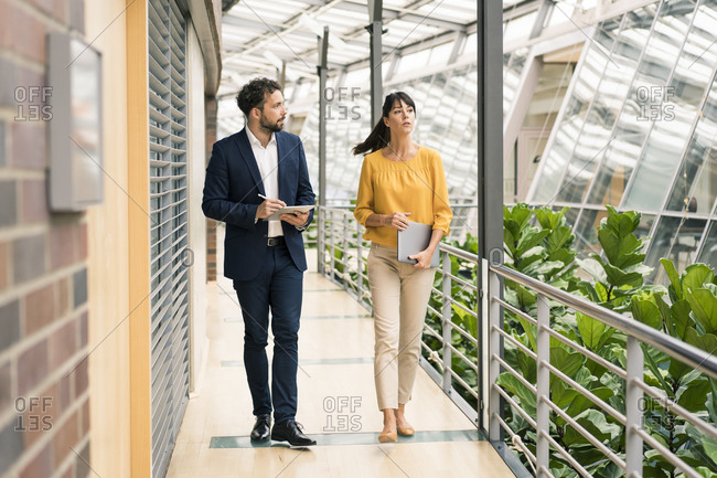 Male entrepreneur discussing while walking with female colleague in office corridor