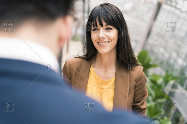 Mature businesswoman smiling while looking at male colleague during office meeting