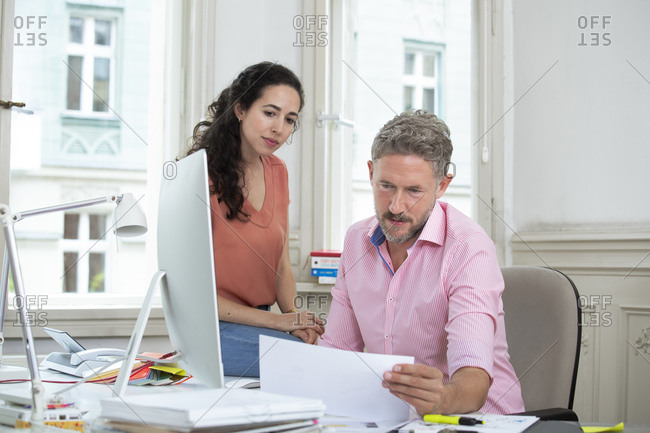 Male entrepreneur reading document sitting by female colleague in office meeting