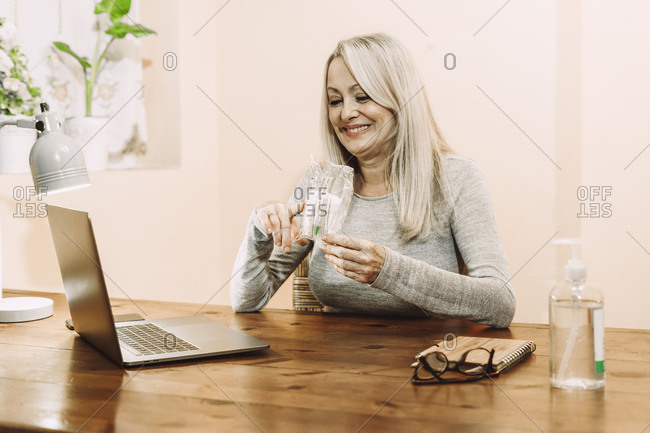 Smiling senior woman holding medical sample during online consultation at home
