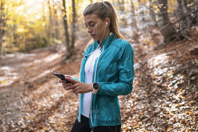 Sportswoman with in-ear headphones using mobile phone while standing in forest