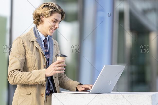 Smiling businessman with coffee cup working on laptop while standing outdoors