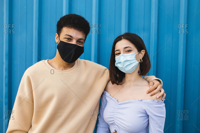 Boyfriend and girlfriend with protective face mask standing against blue wall