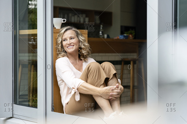 Female entrepreneur day dreaming while sitting at doorway of office cafeteria