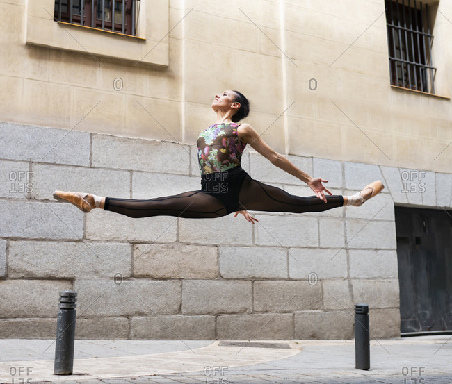 Dancer wearing leotard dancing while jumping with legs stretched on footpath