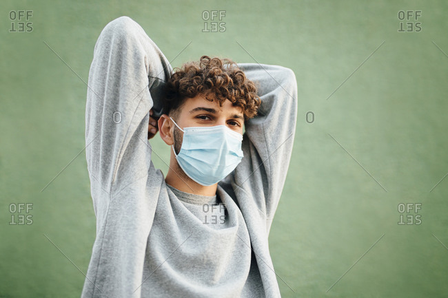 Young man with hands behind head against green background during coronavirus