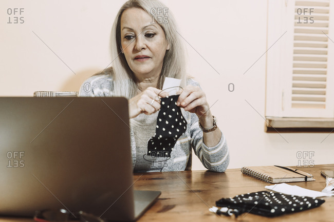 Senior woman holding protective face mask while online consultation at home