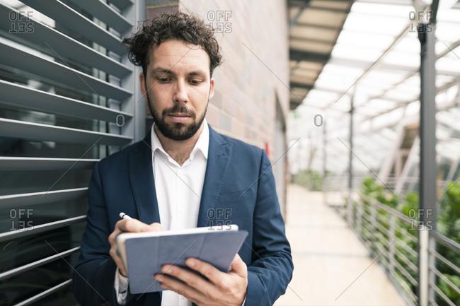 Male entrepreneur using digital tablet while standing in corridor of office