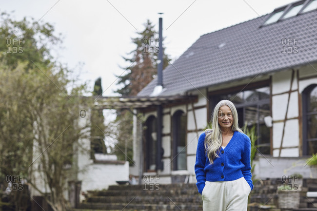 Smiling mature woman with hands in pockets standing against built structure