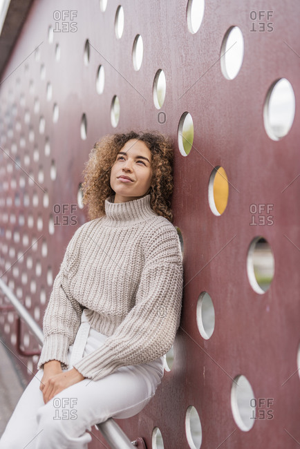 Thoughtful young Afro woman sitting on railing against maroon metallic wall