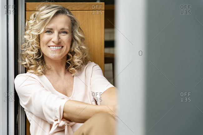 Smiling businesswoman with blond hair siting at doorway of office cafeteria